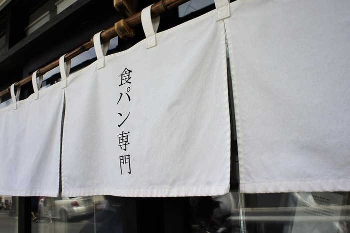 鎌倉から江ノ電に乗って、長谷~極楽寺の中間地点にある、古民家に掲げられた白い暖簾が目印のブレッドコード。こちらのブレッドコードは、世田谷にある最高級パン専門店「ルセット」を母体に持つ、鎌倉にある大人気のブレッドカフェ「ルセット」直営の食パン専門店なんですよ。