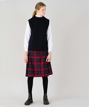 ひざ丈の赤いチェックスカートには、ベストを合わせてトラッドなスタイルに。足元にはブーツを合わせて大人っぽく仕上げましょう。