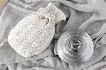 ざっくりとしたケーブル編みの専用カバーがかわいらしい。素材は超長綿の「落ち綿」を使用。空気を含んで温かく、落ち綿独特のしっとりと柔らかな質感が指先から包むように温めてくれます。