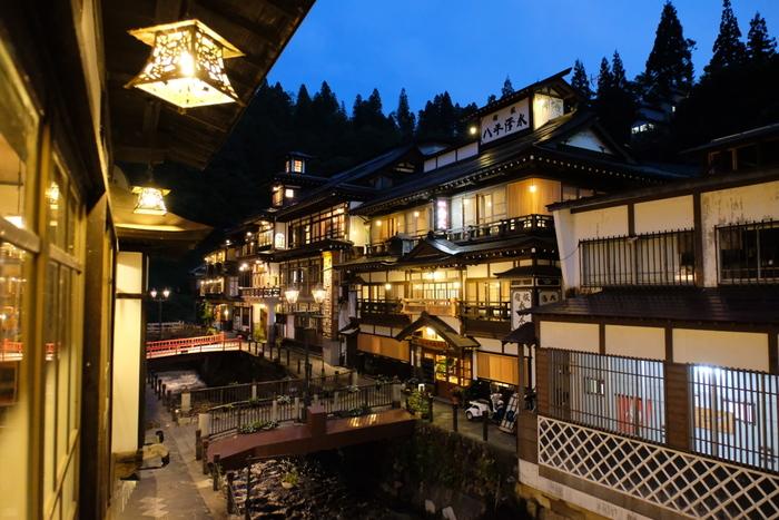 """温泉街の、どこか懐かしくて""""昭和""""にタイムスリップしたかのような街並みも魅力のひとつ。木造の老舗旅館を眺めながら温泉街を流れる川沿いを歩いていると、非日常気分を味わうことができそう…♪ 昼間だけでなく、夜のほんのり明かりが灯る時間の温泉街も素敵です!"""