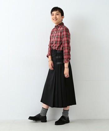パッと目を引く赤のチェックはかわいくなり過ぎないように黒のスカートでまとめて。スカートと靴下のバランスも参考になります。