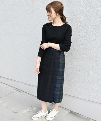 グリーンのプリーツスカートは前面のブラックが一癖あるデザイン。色味を押さえて大人のトラッドコーデに。