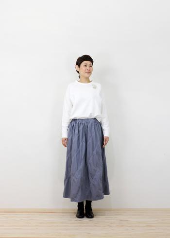 トップスをボトムにタックインするだけで、腰の位置が高く見え足が長く、スタイルよく見えます。白のスウェットトップスとロングスカートとのシンプルな組み合わせもイマっぽさを感じるコーディネートに。