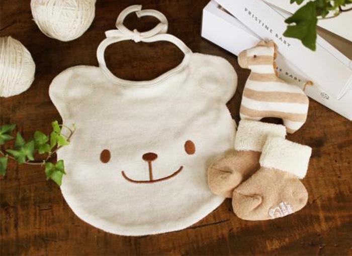にっこり笑ったクマさんの顔が可愛らしいこちらのスタイは、オーガニックコットン100%のパイル素材。柔らかく気持ちのいい手触りは赤ちゃんのお口周りを拭くのにも安心ですし、面積が広めで食べこぼしもしっかり防ぎます。首元とお腹回りの2カ所をヒモで結んで固定するので、赤ちゃんがハイハイしても生地が前に垂れず、引っ掛かって転倒してしまう心配もありません。