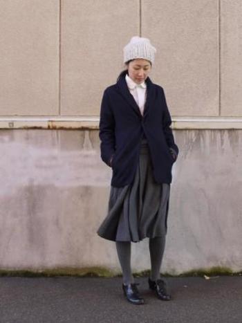 ネイビーのジャケットに、グレーのスカートとタイツを合わせたトラッド風のスタイル。インナーのホワイトシャツとニット帽で、明るさのポイントを上手に作っています。