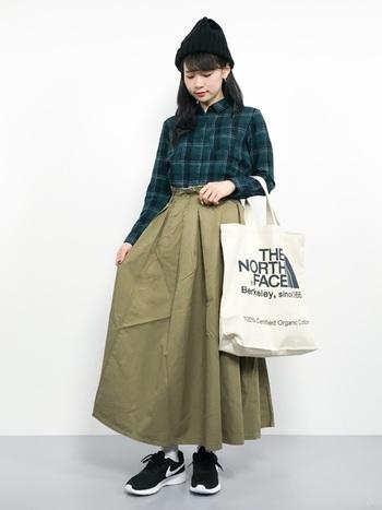 同色系のカーキを組み合わせたコーデはシャツインしたスタイルが今っぽい。ボリュームのあるスカートの足元は軽やかなスニーカーが◎。