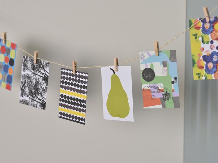"""天井や壁に飾る""""ガーランド""""は、空間を立体的にセンス良く飾ることができます。麻の紐やウッドピンチさえ用意すれば、あとはポストカードや写真などを飾るだけ。簡単なのでぜひ試してみてください!"""
