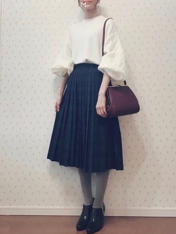 ブラックウォッチ柄のミモレ丈プリーツスカートとアンクルブーツを合わせてレディライクに。