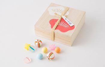 缶ではありませんが、お正月のご挨拶にぴったりの「めで宝飴」も素敵。紅白梅文様の木箱に、明るくかわらしい飴々が入っています。宝箱のような木箱は、贈る側も贈られた側も笑顔になりますね。  木箱はカードや小物をしまっておくのに重宝しそうなサイズです。