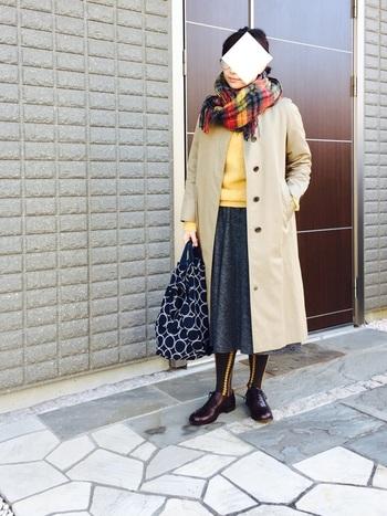 トレンチコートとスカート、ニット、ストールとトータルでカラーリングも参考になる素敵なコーディネートです。前を開けて着る時には、ストールの柄と服の色を合わせておくとよりこなれ感を出すことができます。