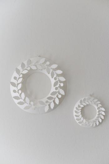 玄関の壁に飾られている純白のリースは、プロダクトデザイナー・伊藤千織さんが手掛けたデザイン。ポリプロピレンを主原料にした合成紙でできており、一枚の紙を組み立てると立体的なリースが現れます。「ひいらぎ」をモチーフにしたMサイズ、「月桂樹」のSサイズ、どちらも繊細で柔らかな陰影が美しいですね。