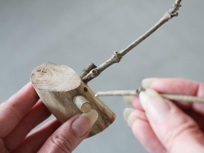 はじめに中枝(頭)の1/3くらいを斜めにカットし、切り取った先端の部分を赤でペイントします(赤鼻の部分になります)。次にグルーガンで頭に耳をつけて、角に使う枝と同じ大きさの穴をあけます。穴をあけたら枝の先端にグルーガンを付けて、写真のように穴に差し込みます。