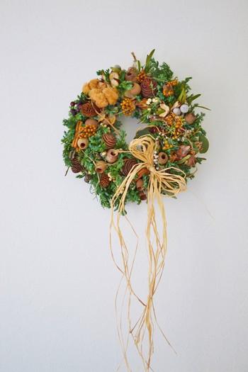 たくさんの花材がたっぷりと盛り込まれて楽しい雰囲気が溢れだすキュートなクリスマスリースです。ラフィアのリボンを長く垂らすと、広がりが感じられますね。