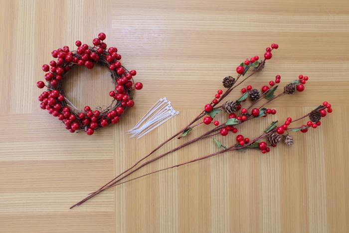 シンプルな赤い実のミニリースをベースに、ナチュラルキッチンの松ぼっくりの入った枝をプラスしていきます。