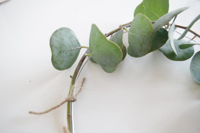 1本100円で購入したというユーカリの枝は針金に沿うようにして、麻紐で留めていきます。