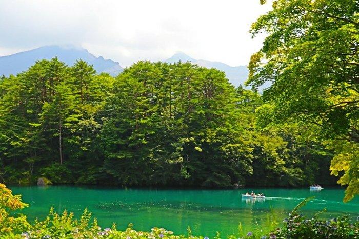 毘沙門沼は、五色沼の中で最も広大な湖沼。エメラルドグリーンに染まった沼の背景には、磐梯山がそびえたちます。ボートで遊泳することもでき、自然と密に触れ合うことができます。