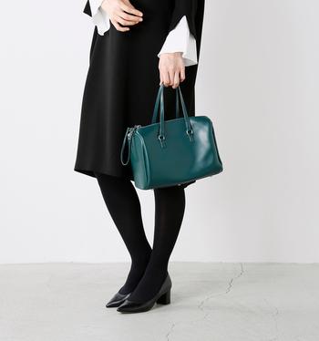 小型のボストンバッグのようなフォルムが愛らしいトートバッグ。コンパクトなサイズ感で、フォーマルなシーンでも違和感無く持つことができます。スクエア型ですが角ばった全体的に丸みをおびていて、フェミニンな装いにもマッチ。深く美しいグリーンが、ブラックドレスの差し色として効いています。