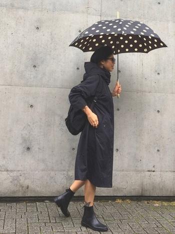 オールブラックのコーディネートで、白と黒の水玉模様の傘をポイントに効かせて。