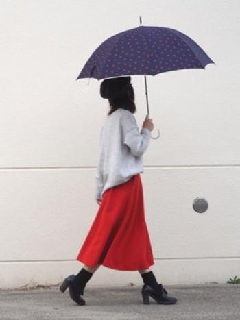 グレーのセータと鮮やかな赤のスカートのコーディネートに、ネイビー×水玉柄の傘を合わせた大人のスタイル。スカートと水玉の色がさり気なくリンクしています。