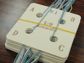 まずは、図案の通りにカードに縦糸を通し数字の順番に重ねていきます。手前側と奥側で糸の端を結んで固定。このとき糸の束をとかしてきれいに揃えることがポイント。