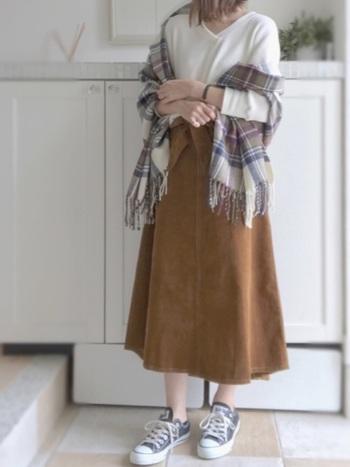 ホワイトのプルオーバーにキャメルのスカート。この2つをキレイにつなぐのは、洋服と同じ色をインクルードしたチェック柄ストールです。