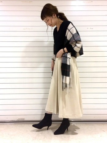 ブラックのニットにホワイトのフレアスカート。プレーンな無彩色の着こなしも、チェックのストールがあることで、グッと奥行きが生まれています。