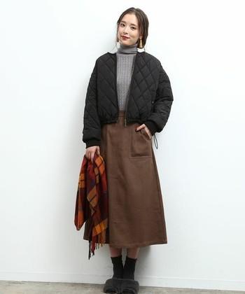 少し長めのスカートには、ミニマルサイズのアウターが好バランス!グレーのタートルニットと褐色のスカートという朴訥な合わせには、キルティングジャンパーを投下して、ほんのりスポーティー要素をプラスします。