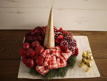 クリスマスリースはドアや壁に飾るのはもちろん、中央にキャンドルを通して、テーブルや棚に乗せるのもおすすめ。りんごやチェックリボンのリースは、食卓にもぴったりです。