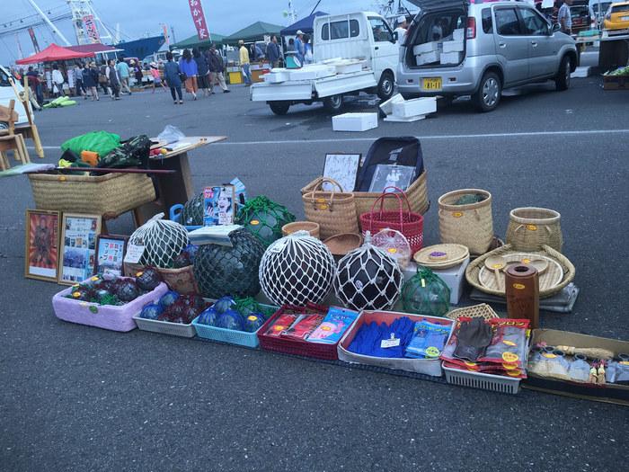 食べ物だけでなく雑貨も数多く売られている朝市では、漁港ならではのこんなものも。真ん中に並ぶネットに包まれたものは、ガラスでできた海の浮き玉。家のインテリアとして楽しめますよ。