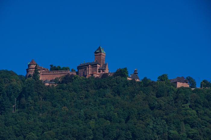 標高760メートルの岩山の頂にそびえるオークニスブール城は、12世紀に要塞として建築された歴史的建造物です。抜けるような青空、要塞化された赤茶色の城塞、城を取り囲む緑の森が調和し、遠くから眺めるオークニスブール城の姿は絶景そのものです。
