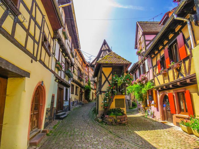 エギスアイムは、フランス最東端でドイツとの国境近くのアルザス地方にある村の一つです。エギスアイムの村の中には、石畳の細い路地、パステルカラーの壁と木骨組の可愛らしい家々、窓辺に飾られている色とりどりの花々が織りなすメルヘンの世界のような景色が広がっています。
