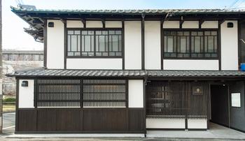 祇園の北側、白川沿いにある「吉祥菓寮 祇園本店」。歴史のある古民家をリノベーションした店舗の外観。  モダンでありながら京の町に馴染み、老舗ならではの威厳も感じられます。