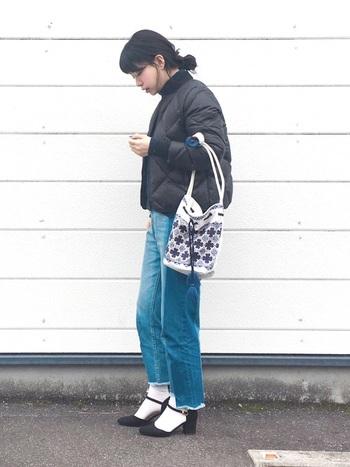 丈が短めのコンパクトなダウンジャケットとカジュアルなデニムパンツのコーディネート。靴下に黒のストラップシューズを合わせて、ちょっぴりおめかしな足元を演出して。