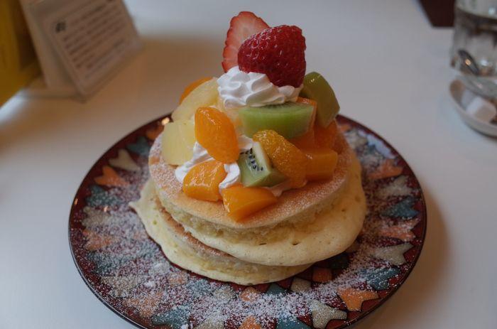 「Cafe ARRIETTY(カフェ アリエッティ)」の「ごほうびパンケーキ」。ふわっふわの生地はお皿を揺らすとプルプル震えるほどの柔らかさ!  上にのっているたっぷりのクリームとフルーツ、口に入れるともっちりふわふわの食感、程よい甘味がうなる美味しさ。一皿ペロリといけちゃいます。