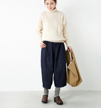 ざっくりとしたアラン編みのニットの持つ可愛らしさを活かすために、「半端丈のワイドパンツ×くしゅくしゅソックス×サボ」の3アイテムでバランス良くまとめたコーデ。ニットの白とパンツのネイビーのカラーリングが、カジュアルなスタイリングに上品さと清潔感をプラスしています。