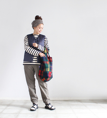 バスクシャツで有名な「SAINT JAMES(セントジェームス)」のボーダーセーターは一枚でも様になりますが、あえてブラックのベストを重ね着することで他と差のつく技ありコーデに。サンダルやヘアバンド、チェック柄のトートバッグなど、カジュアルテイスト満載な小物使いもぜひ参考にしてみてください。