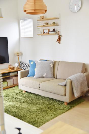 ベージュ系のソファに、ブルーとグレーのクッションを二つ。こちらは「KLIPPAN (クリッパン)」と「ミナ・ペルホネン」 のコラボクッションカバー。置くだけでおしゃれな空間ができあがります。