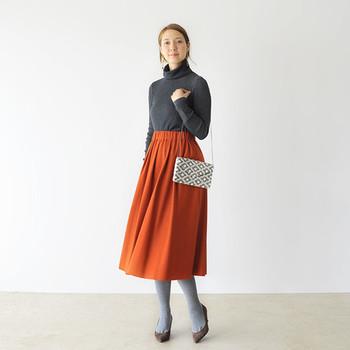ポコポコした模様が可愛らしいワッフル編みのニットに、主役級のオレンジのスカートを合わせた大人ガーリーなスタイル。ニットとタイツをグレーにすることで派手すぎない上品な雰囲気にまとめています。足元はスタイルアップ効果も期待できるパンプスがおすすめ。オシャレしてお出かけしたい日に参考にしたいスタイリングです。