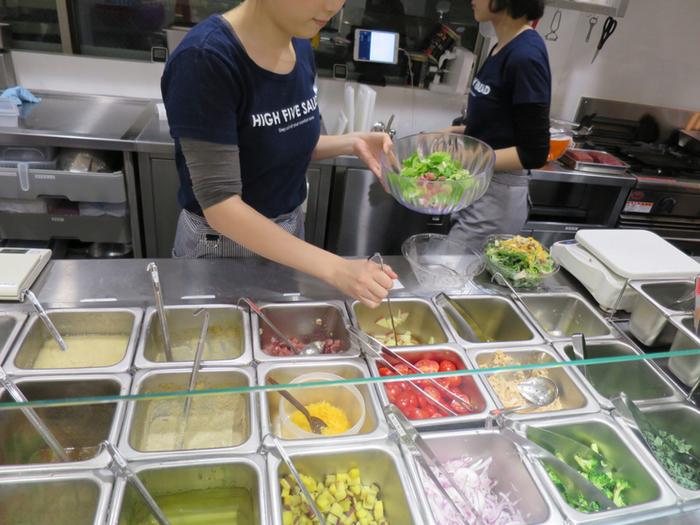 HIGH FIVE SALADは、日本初の「パワーサラダ専門店」。野菜やお肉、シーフード、チーズなどをひとつのボウルに詰め込んだボリューム満点のサラダが食べられるお店として注目されています。オーダーすると目の前で大きなボウルに次々と具材を盛り付けてくれます。  契約農家さんから仕入れた野菜は、どれも「おいしさ・安心・安全」にこだわったものばかり。
