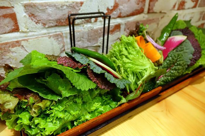「くるむ」のおすすめは、新鮮野菜の数々。15種類ほどの生野菜と、ビビンパやトッポギ、焼肉などをセットにするスタイルが定番。野菜は、えごまやケール、スイスチャード、レッドマスタード、紅芯大根など珍しいものもあり、どんな味か食べてみたくなるものばかり。