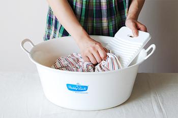 2.せっけん水の中に洗濯物を入れて、利き手と反対の手で洗濯板を固定します。