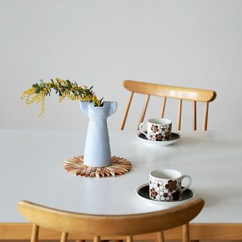 オブジェのようなドレスをかたどった花瓶は、スウェーデンの人気陶芸作家リサ・ラーソンの作品。茎のしなりを美しく演出してくれる、デザイン性の高さは見惚れるほど。 お花のような木製の下敷きがステージとなり、花瓶の存在感を引き立てています。