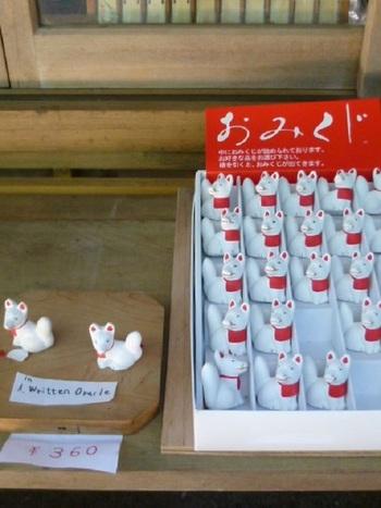 """稲荷神社といえば、狐。神様と同じ、目には見えない存在で""""白狐(びゃっこ)""""と呼ばれています。白狐は、人々に幸福をもたらす神様のお使い。伏見稲荷大社にも表情豊かな狐がたくさんいますのでご注目を。おみくじも、白い狐です。"""