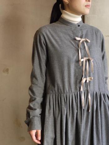 うすい茶色のフロントのリボンは紅茶で染めてあり、スカート部分はたっぷりのタックでボリューム感のあるデザイン。上質な生地ゆえ、柔らかいけれどハリ感のある上質な生地ゆえ、特別な一枚として大切に着たいですね。
