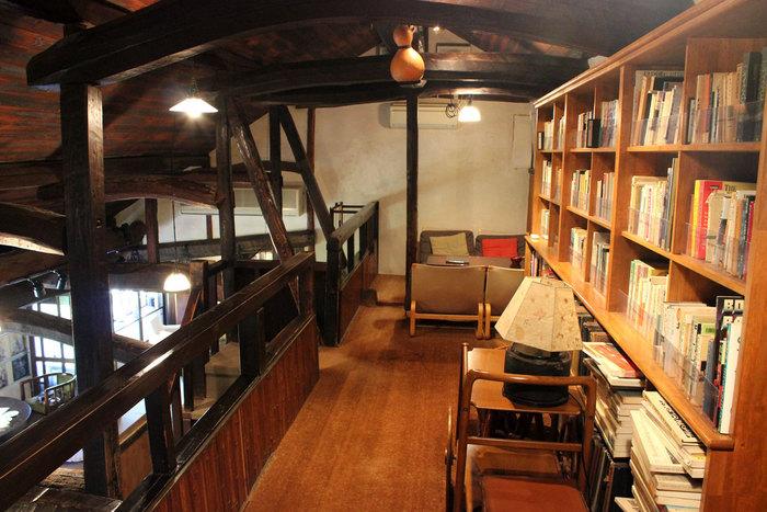 「珈琲・果汁・音楽・読書」のための空間として造られた喫茶室とだけあって、蔵書数も豊富です。緑のガーデンを望む窓際の席も人気ですが、階段上の「ひっそり桟敷」と呼ばれる桟敷席も素敵。