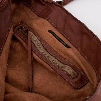 内部にはしっかりと革で淵を補正されたファスナー付のポケットと、ロゴ入りのピューターリングがついています。女性らしい丸い持ち手なので、普段使いでもファッションに合わせやすいアイテムです。
