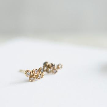 日常に溶け込むジュエリー「ノグチ」のダイヤモチーフピアスです。小さな6粒のダイヤが縦に流れるように配置されていて、石の裏側の金属部分には、光を通す穴が開けられています。