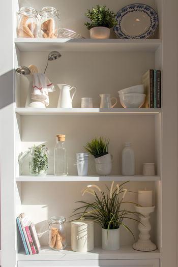 ミルクピッチャーにキッチンツールを収納しちゃうという可愛らしいアイディア。白い棚にはトーンを合わせたものがお行儀よく収まっています。ところどころにグリーンを配置しているのも素敵ですね。