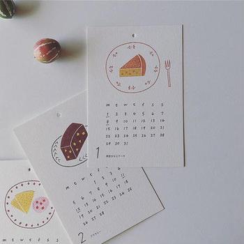 """毎月いろいろなかわいいケーキが楽しめる、北海道釧路市の雑貨屋""""ノラヤ""""さんのイラストカレンダー「ケーキごよみ」です。 見ているだけでお腹いっぱい!素朴であたたかみのある雰囲気がお部屋の空気を和ませてくれます。"""