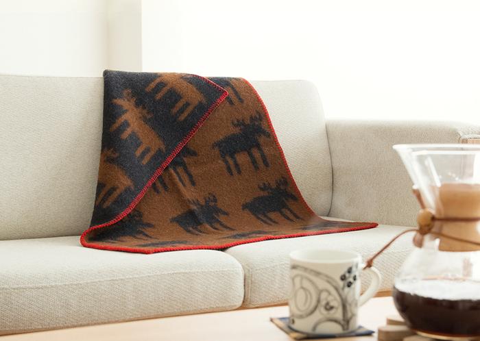こちらはベージュのソファに、クリッパンのブランケットを合わせています。茶色と黒と赤の組み合わせが、ベージュと好相性です。